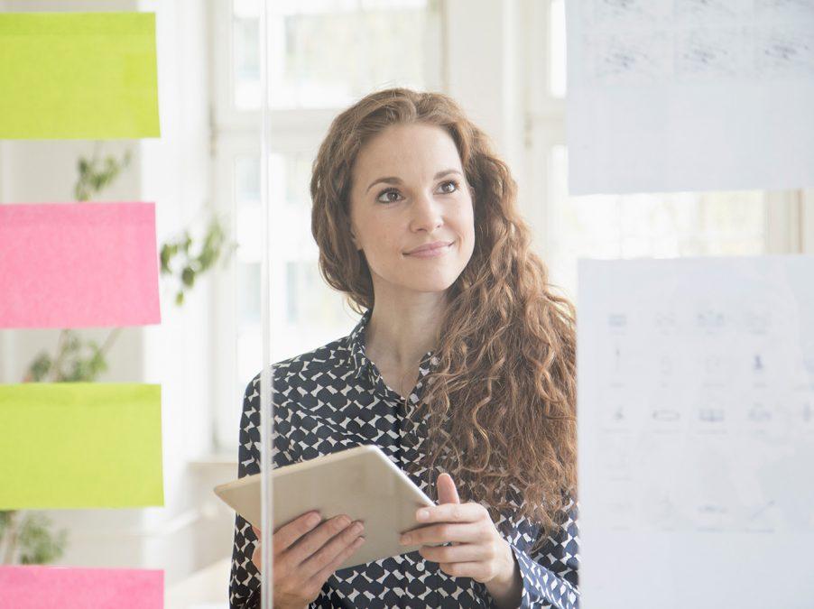 Frau plant mit Notizen auf Glaswand